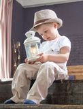 The little boy is sitting on the stairs with a flashlight in hand. Stock Photo