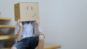 The little boy is sitting on the stairs. He has a cardboard box with different emotions on his head stock video