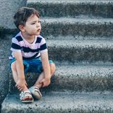 Little boy sitting on stone steps looks down, pensive look and holding his arms outdoors. Space for Text. Retro toned. Summer royalty free stock photography