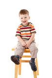 Little boy sitting on stool Stock Images