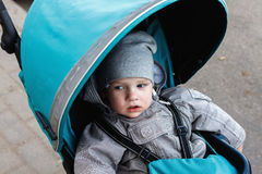 Little boy sitting in a stroller. Baby walk in a pram Royalty Free Stock Images