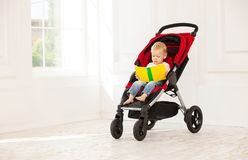 Little boy sitting in stroller and looking at book Royalty Free Stock Photo