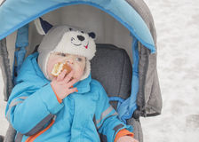 Little boy sitting in the stroller in the winter and eats cake Royalty Free Stock Images