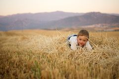 Little boy sitting on the stubble. Royalty Free Stock Photos