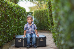 Little boy sitting on a suitcase Stock Photo