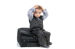 Little boy sitting on a suitcase Stock Photos