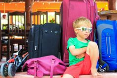 Little boy sitting on suitcases ready to travel royalty free stock images