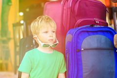 Little boy sitting on suitcases ready to travel royalty free stock photography