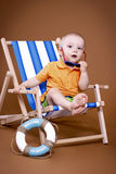 Little boy sitting on the sunbed. Wearing glasses, studio portrait Royalty Free Stock Photos