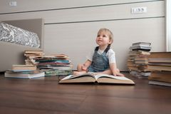 The little boy is sitting with a big book. stock photos