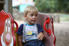 Little boy sitting on a swing. In the park Stock Images