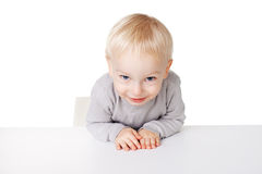Little boy sitting at table Stock Images