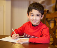 Little Boy Sitting at a Table and Doing His Homework royalty free stock photography