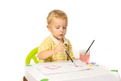 Little boy sitting at the table and draws a brush painting Stock Photos