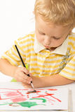 Little boy sitting at the table and draws a brush painting Royalty Free Stock Images