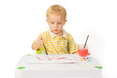 Little boy sitting at the table and draws a brush painting Stock Images