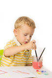 Little boy sitting at the table, draws and dunks brush Royalty Free Stock Photos