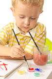 Little boy sitting at the table, draws and dunks brush Royalty Free Stock Photo