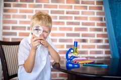Little boy is sitting at a table looking through a magnifying glass royalty free stock image