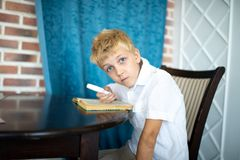 Little boy is sitting at a table looking through a magnifying glass stock photography