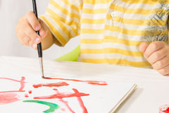 Little boy sitting at a table paints a picture of a white sheet Stock Images