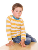 Little boy is sitting on the table. Royalty Free Stock Photography