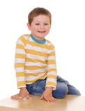 Little boy is sitting on the table. Stock Photography