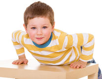 Little boy is sitting on the table. Stock Images