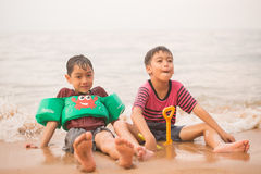 Little boy sitting together on the beach Stock Photo