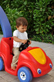 Little boy sitting in toy car Royalty Free Stock Image