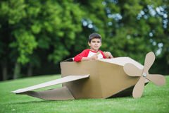 Little boy sitting in toy plane while playing in park Royalty Free Stock Photos