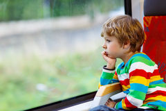 Little boy sitting in train and going on vacations Royalty Free Stock Image