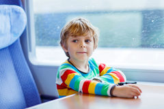 Little boy sitting in train and going on vacations Stock Photo