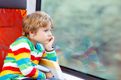 Little boy sitting in train and going on vacations Royalty Free Stock Photography