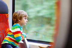 Little boy sitting in train and going on vacations Stock Images