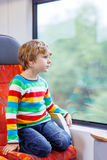Little boy sitting in train and going on vacations Royalty Free Stock Images