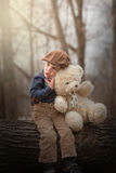 Little boy sitting on a tree and hugging a teddy Stock Images