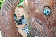 Little boy sitting on trunk of mammoth sculpture. Little blond boy in shorts sitting on trunk of mammoth sculpture in amusement park summer day Royalty Free Stock Photography