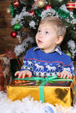 A little boy sitting under the Christmas tree. A little boy sitting under the Christmas tree with gifts. Blond boy. A child in a blue sweater with a reindeer Stock Image