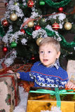 A little boy sitting under the Christmas tree. A little boy sitting under the Christmas tree with huge gifts. He is very happy. Boy in blue sweater Stock Photography