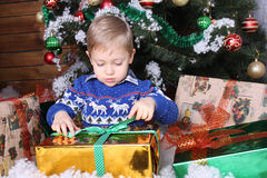 A little boy sitting under the Christmas tree. He opens his presents Stock Images