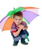 Little boy sitting under umbrella Stock Photo