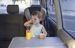 Little boy sitting in van and eating yogurt and orange juice Stock Photos