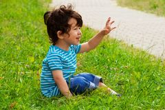 Little boy sitting and waving stock photos