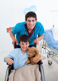 Little boy sitting on wheelchair and a doctor stock image
