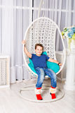 Little boy sitting on white chair Royalty Free Stock Images