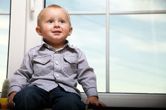 Little boy sitting on window Stock Image