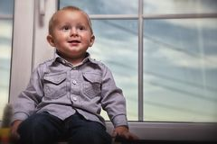 Little boy sitting on window Stock Photos