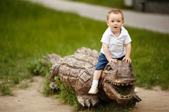 Little boy on a wooden crocodile Royalty Free Stock Images