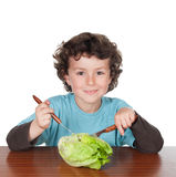 Little boy sitting at the wooden table eating a lettuce Royalty Free Stock Photography